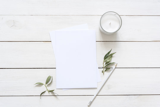 Modern flat lay with card blank space, stationary, candle, leaves, white pencil. Ready for you to insert your text, invitation, wedding or logo. Best for social media, backgrounds, blogs