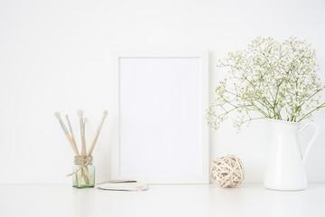 Stylish white frame mockup A4 in interior. Frame mock up background for poster frame for bloggers, social media, lettering, art, design. Indoor, frame on table with white flowers in vase. Summer sea