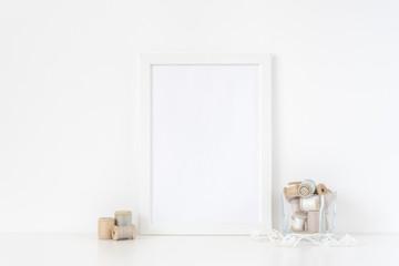 White frame mockup A4 in interior. Frame mock up background for poster or photo frame for bloggers, social media, lettering, art and design. Indoor, frame on table with transparent vase. Poster