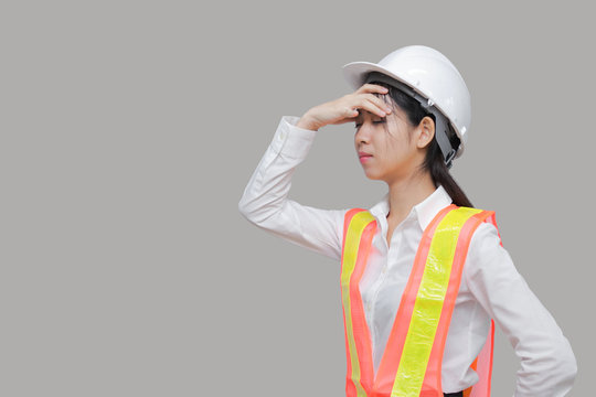 Tired overworked young Asian woman worker wiping sweat posing on gray isolated background.