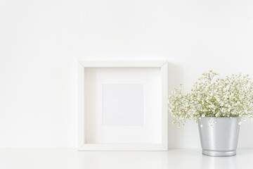 Stylish white square frame mockup in interior. Frame mock up background for poster or photo frame for social media, lettering, art and design. Indoor, frame on table with flowers in vase, stationary.