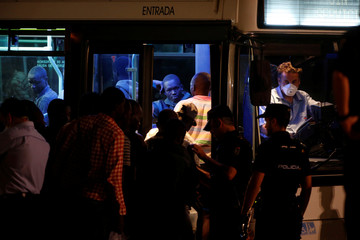 Migrants are led by Spanish police officers into a bus moving towards a sports center after arriving on a rescue boat at the port of Malaga