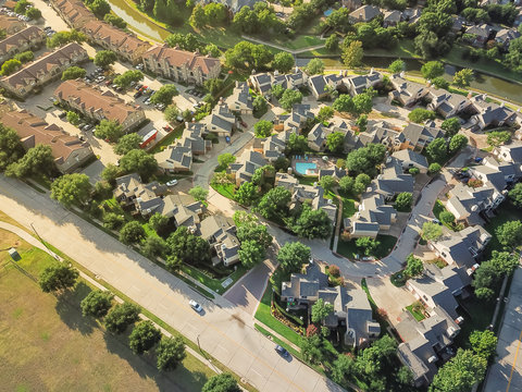 Aerial view apartment complex building with swimming pool in urban subdivision in Irving, Texas, USA. Green suburb growing with a lot of trees and canal. Environmentally friendly living neighborhood