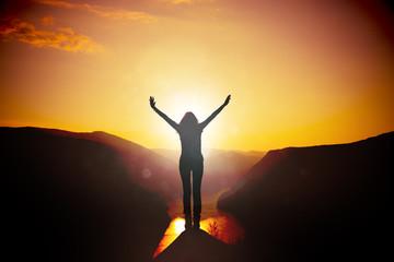 Frau mit ausgebreiteten Armen bei Sonnenuntergang