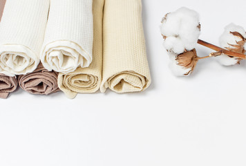 Multicolored clean towels with a branch of cotton on a white background top view with copy space. Texture of cotton, waffle towel, textiles. Towels for kitchen or Spa concept.