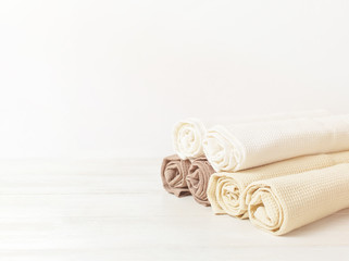 Multicolored clean towels on a light wooden background with copy space. Texture of cotton, waffle towel, textiles. Towels for kitchen or Spa concept.