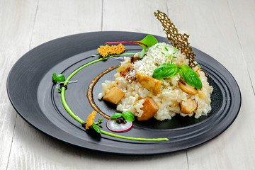 Gourmet Italian risotto cooked in a vegetable broth with porcini mushrooms and parmesan cheese served on an expensive exclusive plate.