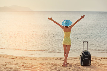Beautiful young woman standing with suitcase on the wonderful sea background, concept of time to travel
