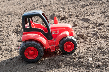 A red tractor goes uphill through the field, the soil