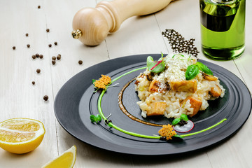 Creamy baked mushroom risotto from Italy on an exclusive beautiful plate. Vegetarian Italian meal made of rice, vegetable broth, porcini mushrooms and parmesan cheese.