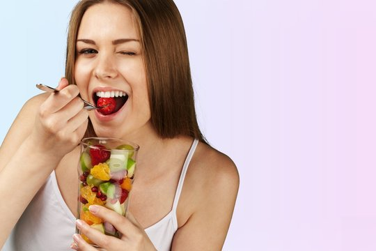 Young woman eating fruits from glass on