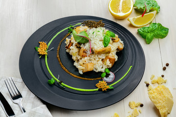 Creamy baked mushroom risotto from Italy on an exclusive beautiful plate. Vegetarian Italian meal made of rice, vegetable broth, porcini mushrooms and parmesan cheese. Top view shot.