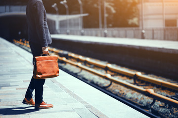 Cropped picture of man standing at metro station. Elegant guy in suit standing at subway station and holding brown leather bag while waiting for train to arrive.