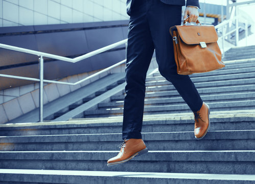 Businessman making steps down stairs. Cropped shot of man wearing elegant suit and shoes walking down stairs and holding brown leather bag in his hand.