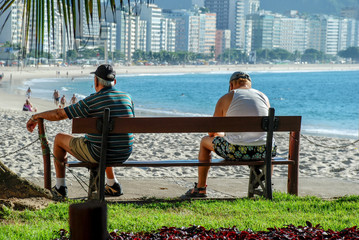 Two elderly people sitting on the bench at Copacabana beach