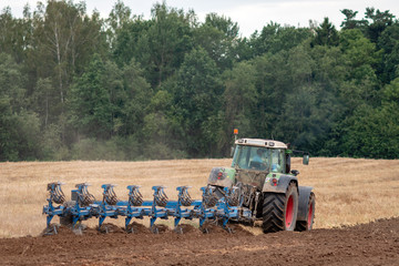 A tractor with a plow treats the soil. View from the back.
