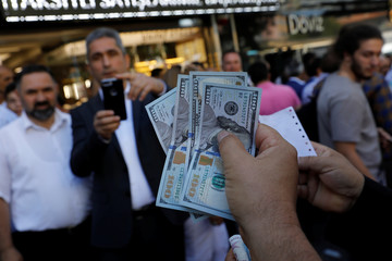 A businessman holding U.S. dollars poses for his friend in front of a currency exchange office in Ankara