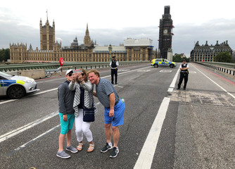 Tourists pose for a group selfie at the police cordon on Westminster Bridge after a car crashed outside the Houses of Parliament in Westminster, London