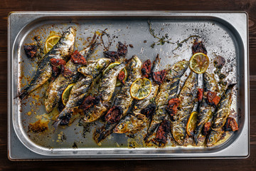Delicious baked sardines on a tray. Healthy meal made of fresh fish. Directly above top view shot.