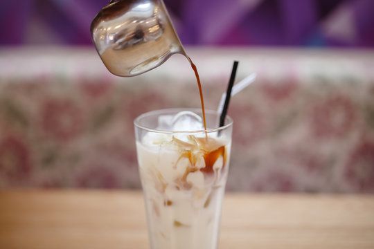 Barista prepares summer cold coffee with ice and milk in transparent glass.