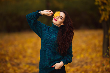 Happy young woman in park on sunny autumn day. Cheerful beautiful girl in green sweater outdoors among yellow leaves on beautiful fall day.