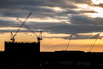 Silhouette Crane and building At Construction Site During Sunset.