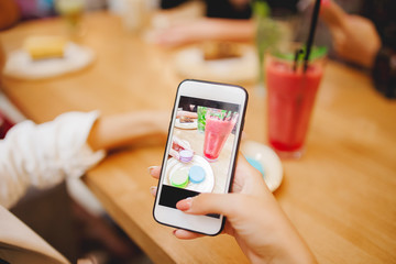 Young woman blogger is making mobile food photo. Concept content for instagram