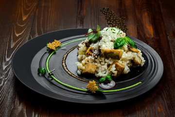 Tasty risotto cooked in a vegetable broth with porcini mushrooms and parmesan cheese on a beautiful plate. First class Italian dish on a wooden table.