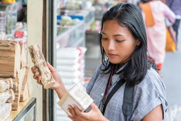 Asian woman chooses thanakha at the market. Young woman buys thanaka powder in bundle and thanakha logs.