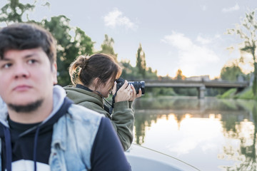 Woman with a camera takes pictures of the nature from the boat, sailing along the river