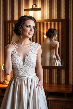 Portrait of a beautiful bride in a wedding dress standing in a room near a mirror. Vertical frame