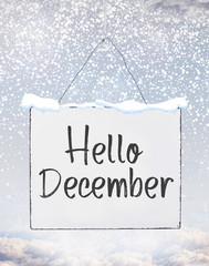 Hello December text on white plate board banner with cold snow flakes qoutes