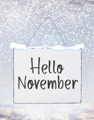 Hello November text on white plate board banner with cold snow flakes qoute