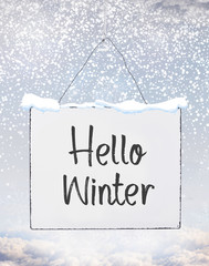 Hello Winter cold season handwritten text on metal board banner with snow flakes