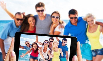 Happy friends making selfie on beach on summer day