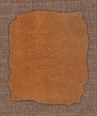 Piece of leather on the fabric linen textile texture