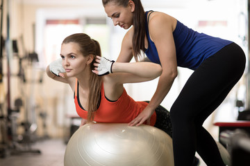 Fitness trainer helping young girl doing back exercises in gym