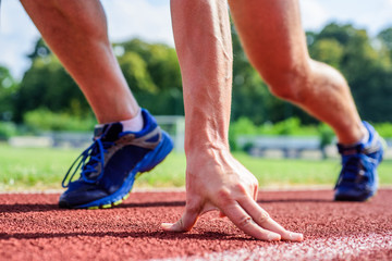 Runner ready to go close up. Ready steady go concept. At beginning of great sport career. Hand touch track path close up. Hand of sportsman on running track low start position. Starting point
