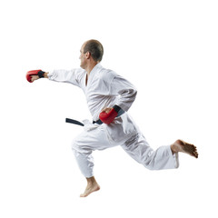 On a white background the sportsman with red overlays on hands trains a blow with his hand in a jump