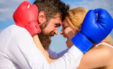 Family life happiness and relation problems. Reconciliation and compromise. Fight for your happiness. Man beard and girl cuddle happy after fight. Couple in love boxing gloves hug blue sky background