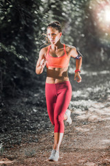 Young female athlete jogging in the park