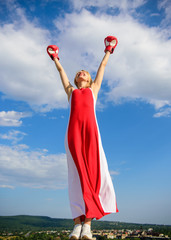 Femininity and strength balance. Woman red dress and boxing gloves enjoy victory. She fighter female rights. Lady fighter enjoy celebrate victory. Satisfied free girl boxing gloves. Winner concept