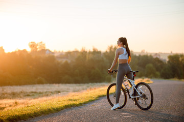 Rear view of young brunette fit woman in sportswear with bicycle on the countryside road near the field on sunset.