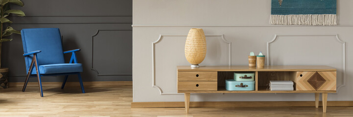 Panorama of a vibrant blue armchair by a gray wall and a retro, wooden sideboard by a white wall with molding in a minimalist living room interior Fotoväggar