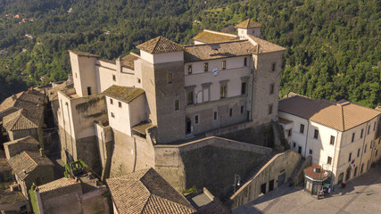 Aerial view of Castelnuovo di Porto castle, near Rome in Italy. The building has a square shape with four towers at the corners. On the facade there is a clock and around the houses of the village.