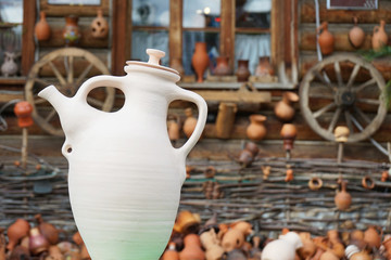 Ceramic white jug on the background of an old wooden house.