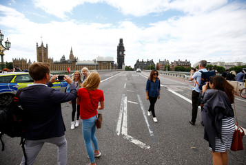 Tourists pose for a picture at a police cordon on Westminster Bridge after a car crashed outside the Houses of Parliament in Westminster, London