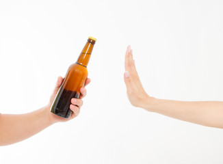 female hand reject a bottle of beer isolated on white background.anti alcohol concept. Copy space