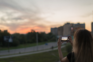 Girl taking photos on smartphone from the roof