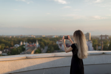 Girl taking photos on smartphone from the roof at sunset